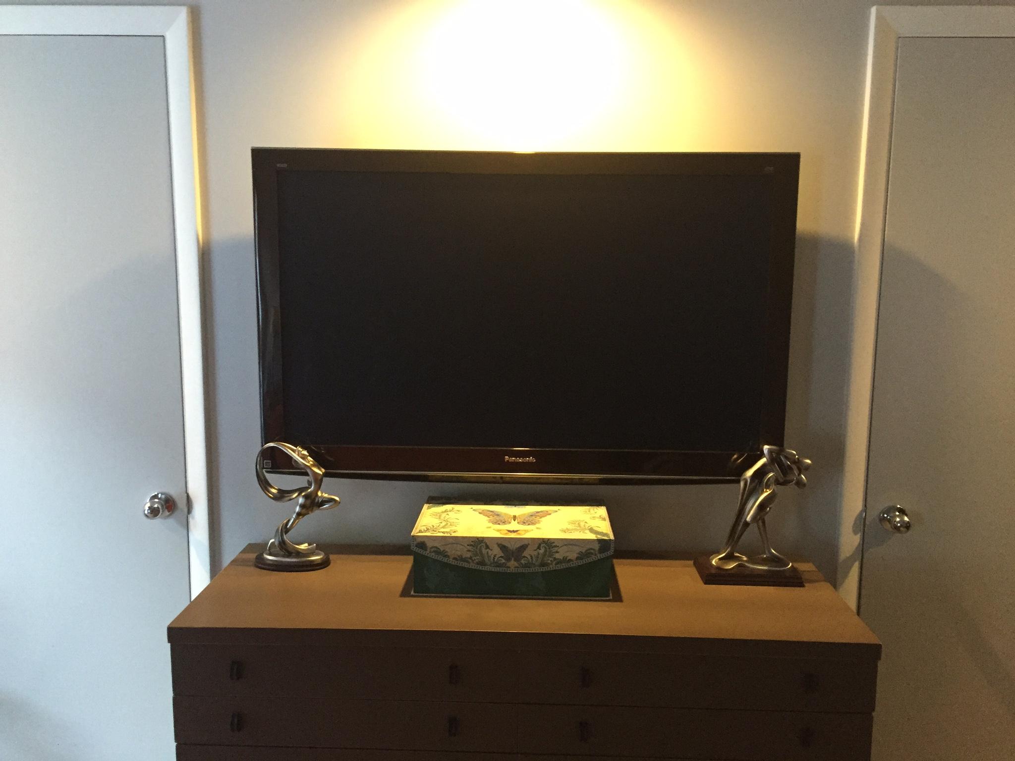 Swivel TV mount in bedroom above dresser -